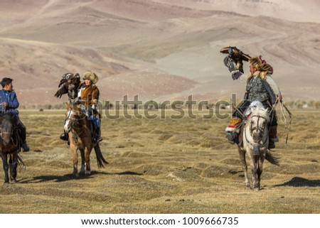 SAGSAY, MONGOLIA - SEP 28, 2017: Eagle Hunter teaches her young daughter hunting with birds of prey to the hare in desert mountain of Western Mongolia. #1009666735