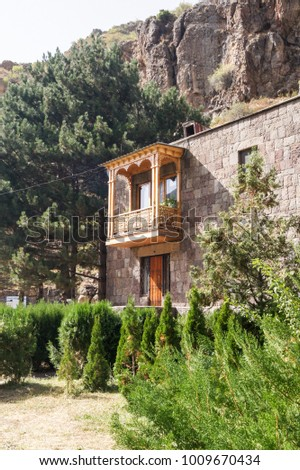 Wooden balcony on a stone wall. #1009670434