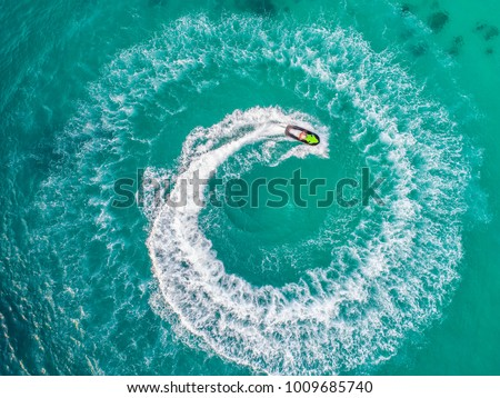 People are playing a jet ski in the sea.Aerial view. Top view.amazing nature background.The color of the water and beautifully bright. Fresh freedom. Adventure day.clear turquoise at tropical beach. #1009685740