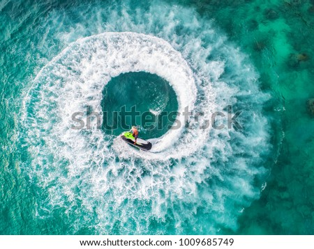 People are playing a jet ski in the sea.Aerial view. Top view.amazing nature background.The color of the water and beautifully bright. Fresh freedom. Adventure day.clear turquoise at tropical beach. #1009685749