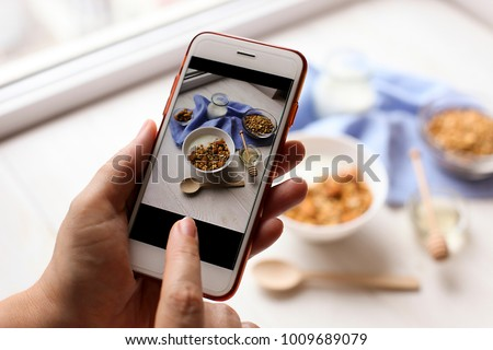 Young woman food blogger takes photo for blog, pic of bowl with Greek yogurt homemade granola, mixed nuts, almond, cashew, hazelnut. Healthy vegetarian protein diet breakfast. Selective focus, closeup