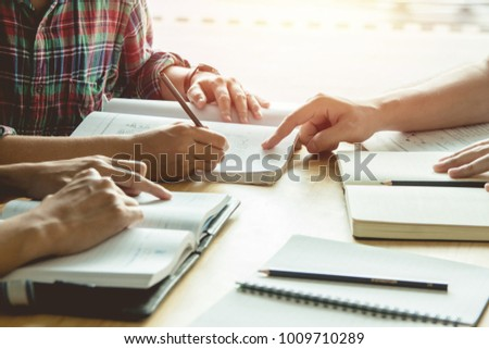 Asian young man,Homosexuality or woman sitting pointing studying examining. Tutor books with friends. Young students campus helps friend catching up and learning. People, learning, education #1009710289