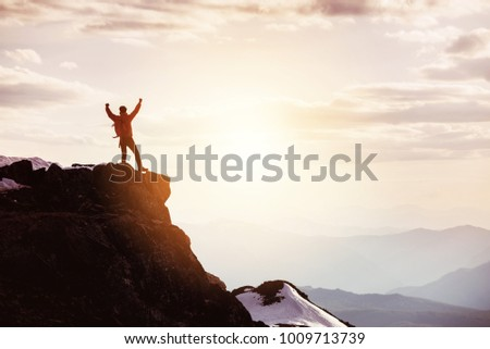 Hiker or traveller stands in winner pose at mountain top against mountains and sunset. Win or success concept #1009713739