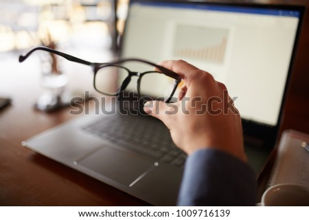 Close-up isolated shot of mans hand holding eyeglasses in front of laptop screen with charts and diagrams. Poor eyesight threatment theme. Computer glasses. #1009716139