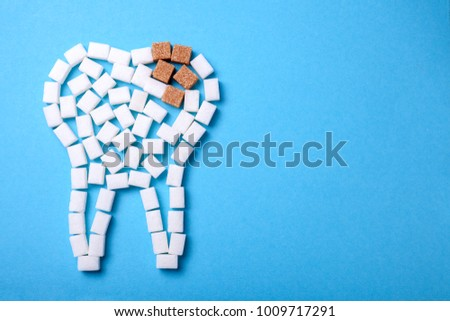 Sugar destroys the tooth enamel and leads to tooth decay. Sugar cubes are laid out in the form of a tooth and brown sugar symbolizes caries. Copy space for text #1009717291