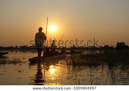 Relaxing traditional tranquil mokoro boat trip during sunset at Okavango Delta, Botswana, Africa.