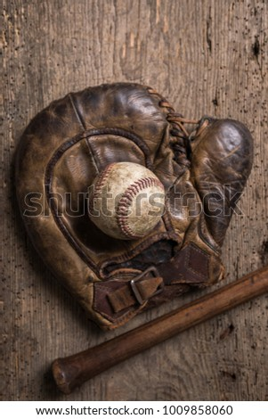 Vintage weathered baseball,glove and bat on a rustic wooden board Royalty-Free Stock Photo #1009858060