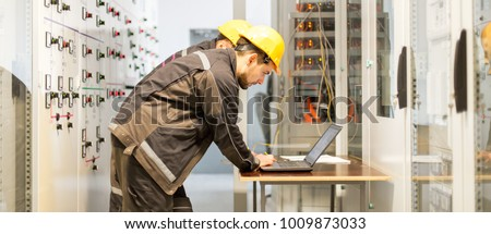 Two maintenance engineers inspect relay protection system with laptop computer. Bay control unit. Medium voltage switchgear #1009873033