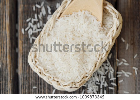 White long grain rice on a wooden spoon #1009873345