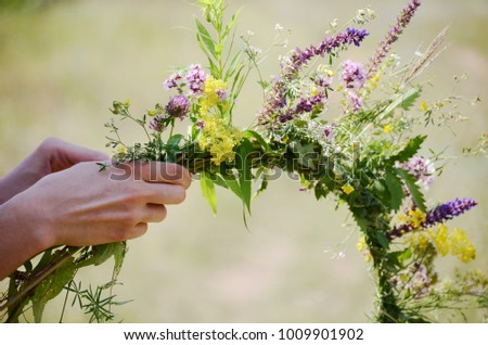 The girl makes a wreath at the head. The process of weaving a wreath with herbs and wild flowers. Summer. Spring #1009901902