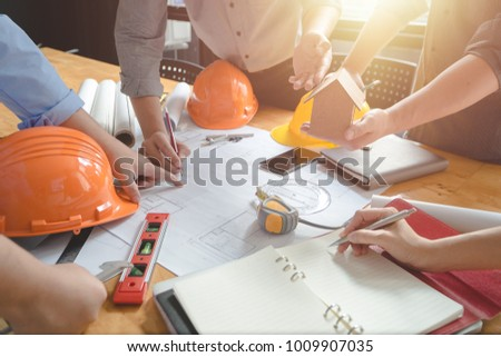 Team of architects or engineer discussing on desk with blueprint about new startup project on desk. Team group on construciton site check documents and business workflow.Selective focus. #1009907035