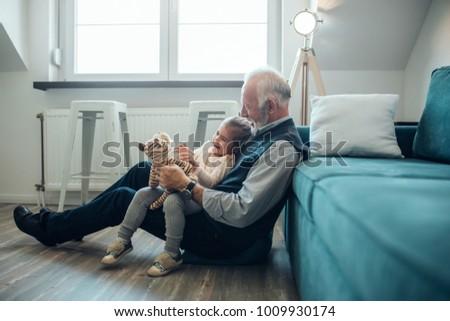 Elderly man holding his granddaughter Royalty-Free Stock Photo #1009930174