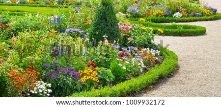 Lush flower beds in the summer garden. A bright sunny day.Wide photo. #1009932172
