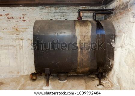 Old heating oil tank in dingy dank basement. #1009992484