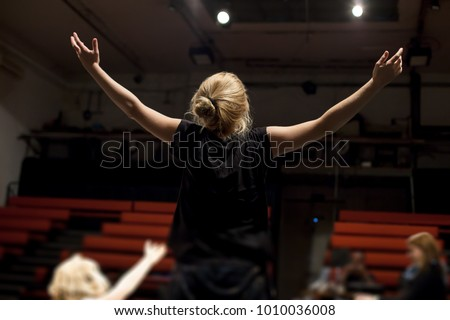 actress rehearsing in front of empty theater Royalty-Free Stock Photo #1010036008
