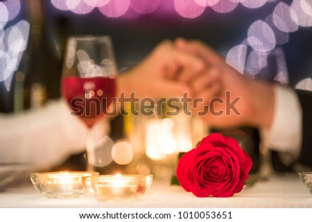 Couple holding hands on a romantic dinner date with focus on rose.  #1010053651