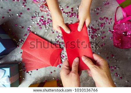 Close up hands of parent giving a red envelope or money red packet to child  .  Chinese new year and Lunar new year festival concept background . Top view . Royalty-Free Stock Photo #1010136766