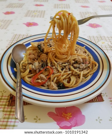 a fork of spaghetti in a plate on the table and picking up. #1010191342