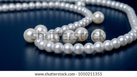 A white pearl necklace before a single background