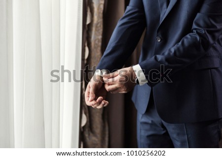Businessman wears a jacket,male hands closeup,groom getting ready in the morning before wedding ceremony #1010256202