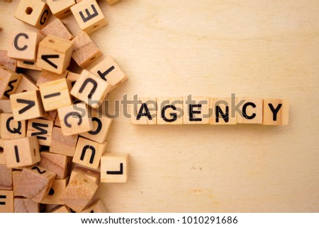 agency word cube on wood background #1010291686