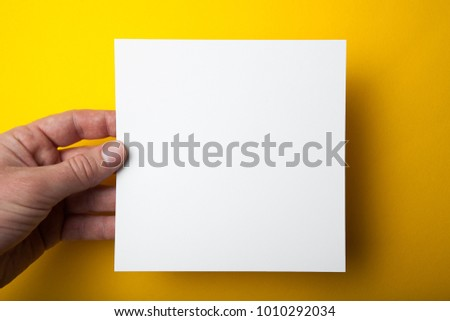 Empty square layout in hand on a yellow background.
