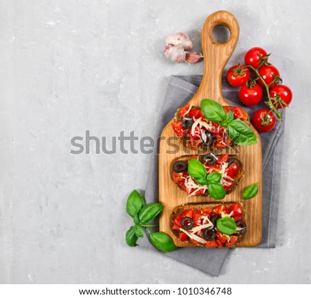 Bruschetta with fresh tomato, basil, cheese and olive on grey background. Top view. #1010346748