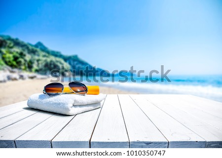 White beach towel with sunglasses on white wooden table. Free space for your decoration of product or text. Blurred landscape of sea and green trees with blue sky.   #1010350747