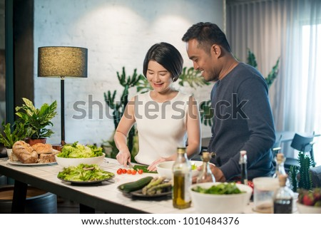 Happy Asian couple preparing food in the kitchen at home. #1010484376