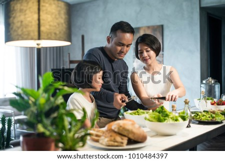 Happy Asian family preparing food in the kitchen. #1010484397