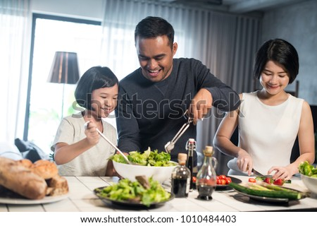 Happy Asian family preparing food in the kitchen. #1010484403