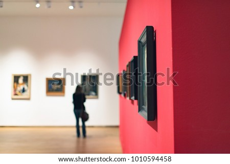 Room in museum with artworks and visitor. Royalty-Free Stock Photo #1010594458