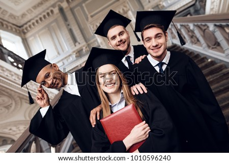 Students in mantles are happy that they finish their studies at the university. They are university graduates. They are very happy about this. #1010596240