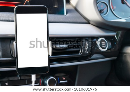 Smartphone in a car use for Navigate or GPS. Driving a car with Smartphone in holder. Mobile phone with isolated white screen. Blank empty screen. copy space. Empty space for text. car interior #1010601976