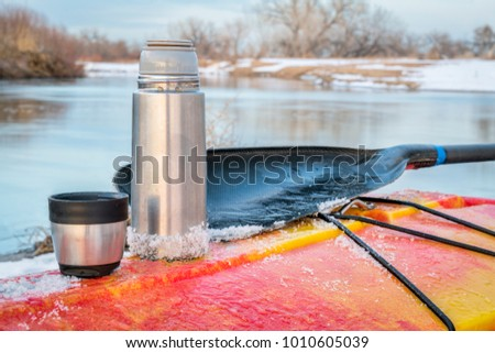 winter kayaking in Colorado - thermos bottle with hot tea on the icy deck of a red whitewater kayak on shore of St Vrain Creek #1010605039