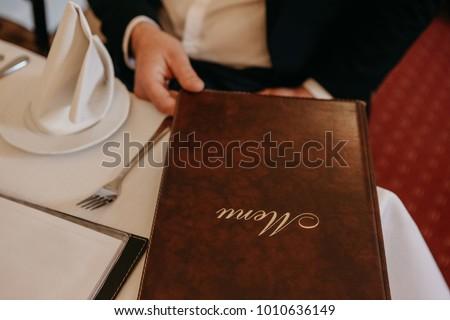 Man in restaurant reading the menu #1010636149