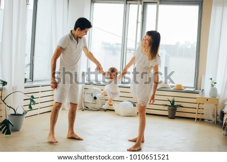 mom and dad entertain the little daughter #1010651521
