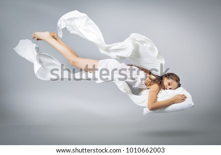 Sleeping girl. Flying in a dream. White linen flying through the air. Light grey background #1010662003