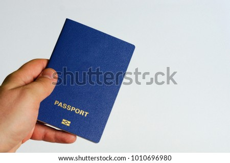 Blue passport in the hands of a man. Isolate #1010696980