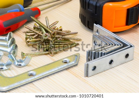 Woodwork tools and screws at the wood planks on yellow background. #1010720401