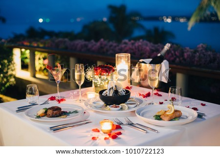 Luxury romantic candlelight dinner table setup for couple in ocean view restaurant on Valentine's day with Champaign & wine glasses and beautiful food decoration.   #1010722123