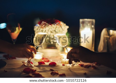 Romantic candlelight dinner for couple table setup at night. Man & Woman hold glass of Champaign. Concept for valentine's day or date. #1010722126
