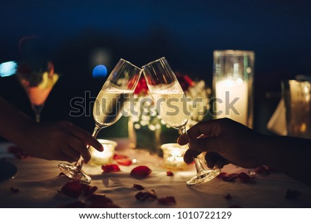 Romantic candlelight dinner for couple table setup at night. Man & Woman hold glass of Champaign. Concept for valentine's day or date. #1010722129