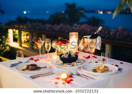 Luxury romantic candlelight dinner table setup for couple in ocean view restaurant on Valentine's day with Champaign & wine glasses and beautiful food decoration.   #1010722132