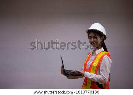 Ladies wore a construction suit. Asian businesswoman using notebook. #1010770180