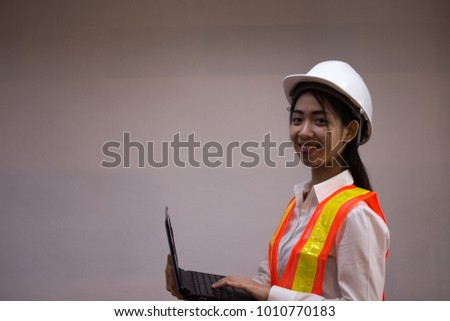Ladies wore a construction suit. Asian businesswoman using notebook. #1010770183
