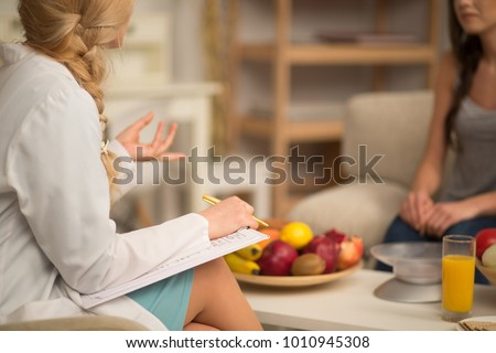 Female nutritionist giving consultation to patient. Making diet plan. #1010945308