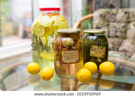 Home canning. Lemon tincture, pickled cucumber and apples in syrup  #1010950969
