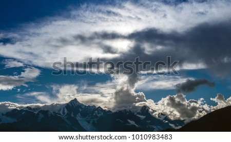 View of Kawagarbo Mounta between Yunnan and Tibet in China under a huge backlight cloud. Kawagarbo is one of the most sacred peaks in the Tibetan world #1010983483