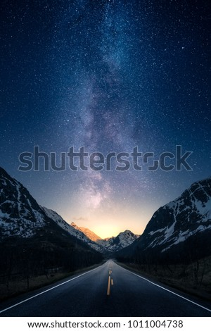 A road leading to distance in a mountain valley with milky way in the backgroung. Royalty-Free Stock Photo #1011004738